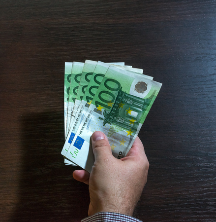 batch of euro: Hand offering one hundred euro bills for bribe