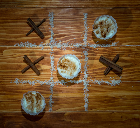 XO Game rice pudding vs. cinnamon sticks on a wooden table