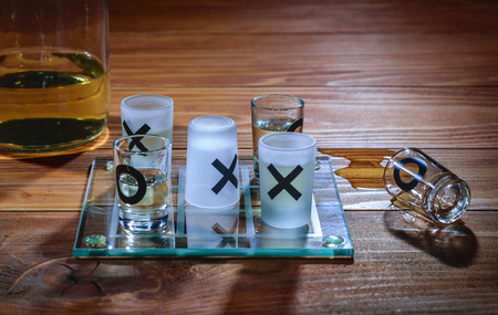 Alcohol wins in xOx game on a wooden table Stock Photo