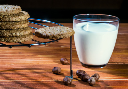 Hazelnut Cookies on a round cooling rack with Milk and Nuts at the old wooden table Stock Photo