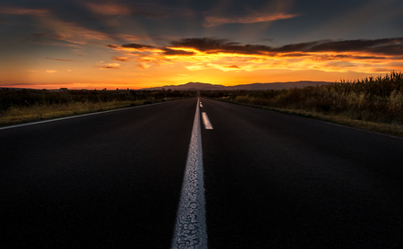 Straight highway road to a dramatic fiery sunset