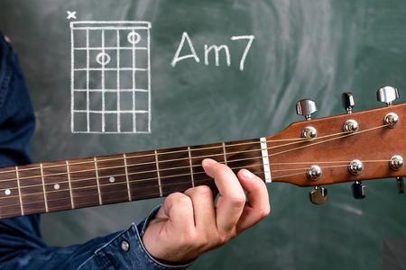 Man In A Blue Denim Shirt Playing Guitar Chords Displayed On.. Stock ...