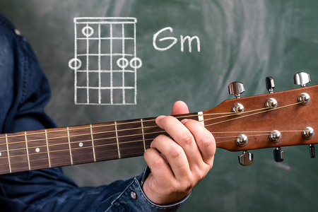 Man In A Blue Denim Shirt Playing Guitar Chords Displayed On.. Stock ...