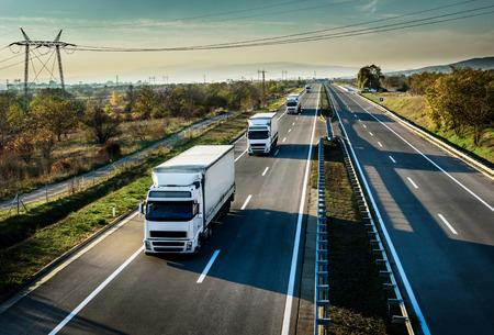 Caravan of white trucks in line on country highway