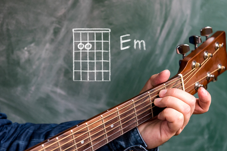Man in a blue denim shirt playing guitar chords displayed on a blackboard, Chord E minor Stock Photo