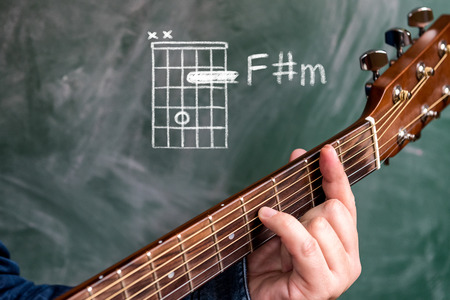 Man in a blue denim shirt playing guitar chords displayed on a blackboard, Chord F sharp minor Stock Photo