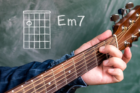 Man in a blue denim shirt playing guitar chords displayed on a blackboard, Chord E minor 7