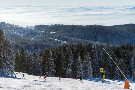 Ski resort Kopaonik, Serbia, ski slope, people skiing down the hill, mountains view