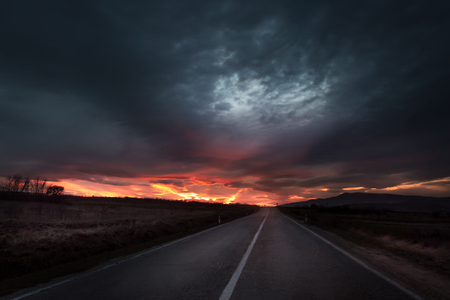 Straight highway road to a dramatic fiery sunset near twilight