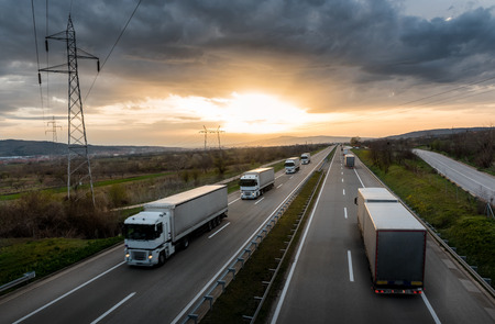 Caravan or convoy of white trucks in line on a country highway at sunset