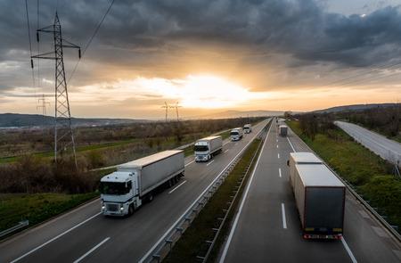 Karawane oder Konvoi von weißen Lastwagen in der Schlange auf einer Landstraße bei Sonnenuntergang Standard-Bild