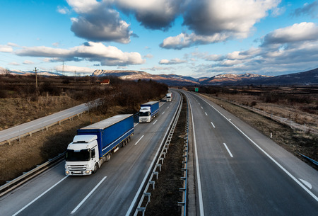 Caravan or convoy of lorry trucks on country highway under a dramatic sky