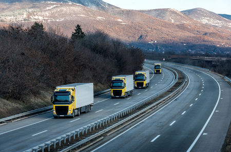 Caravan or convoy of Yellow lorry trucks on country highway under a dramatic sky