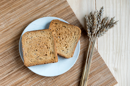 Two Slices of Toast Bread and Ear of Wheat on a Wooden Table Setup Banco de Imagens