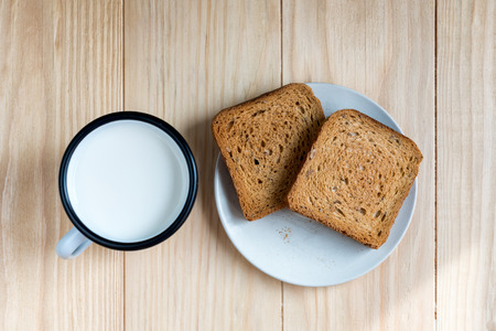 Two Slices of Toast Bread and Tin Mug of Milk on a Wooden Table Setup Banco de Imagens