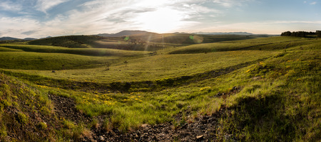 Landscape panorama of Zlatibor Mountain. Green meadows and hills under blue sky with clouds in springtime