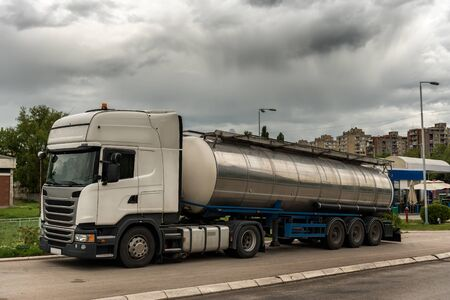 Tank truck parked on by the road in the city, near gas station Banco de Imagens