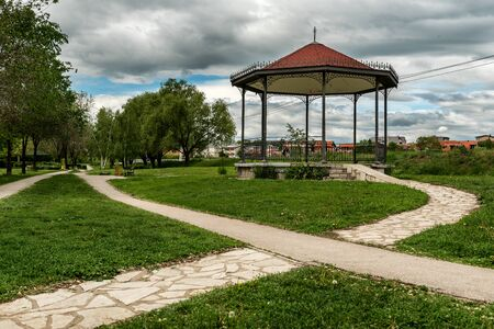 Gazebo or a pavilion on green lawn at the end of a stone pathway