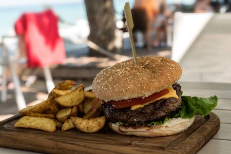 Grilled burger on wooden board with salad and potato chips  with a beach in the background out of focus Banco de Imagens