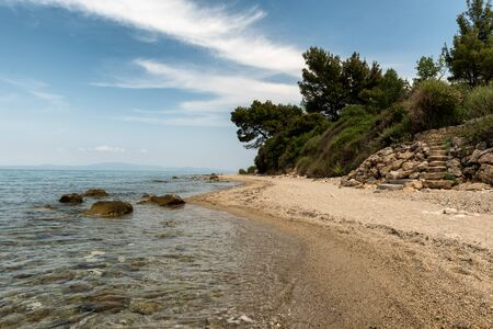 Beautiful Rocky Mediterranean Beach with sand, stones and pebbles with a cliff in the background Banco de Imagens