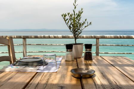 Mediterranean restaurant wooden table with Olive tree, dining setup, salt and pepper and sea view