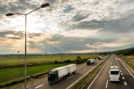 Lorry trucks in line as a caravan or convoy  on country highway under a beautiful sky