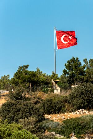 National flag of Turkey on top of the hill against the clear blue sky