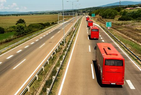 Caravan or convoy of red buses in line traveling on a highway country highway