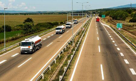 Convoy or Caravan of Tank trucks on a winding Highway traffic through the rural landscape Banco de Imagens