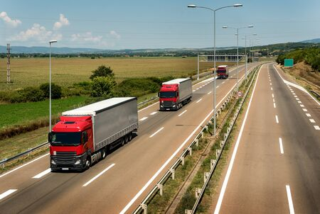 Red Lorry trucks in line as a caravan or convoy  on country highway under a beautiful sky Banco de Imagens