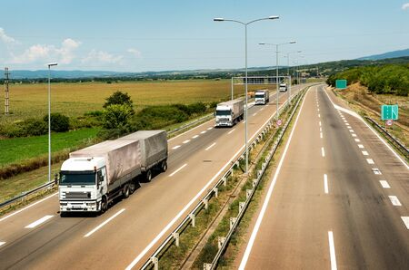 White Lorry trucks in line as a caravan or convoy  on country highway under a beautiful skyc 스톡 콘텐츠