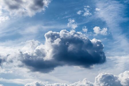 White cumulus clouds and a blue sky with sun rays after a storm