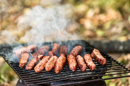 Balkan cuisine Pork Cevapi, grilled minced meat, on the improvised grill