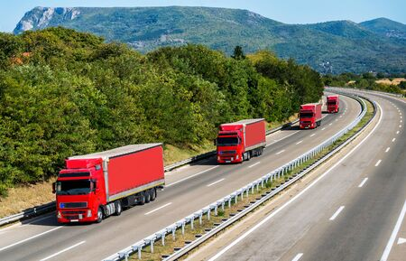 Caravan or convoy of Four red Lorry Lorry trucks in line on a country highway under a beautiful sky
