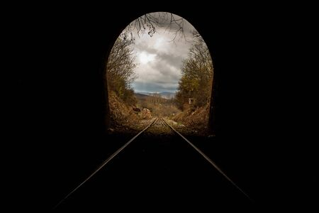 Train tunnel end in picturesque rural scenery. Old railway in cave. Hope of life in the end of the way.Travel and hope at the destination 版權商用圖片