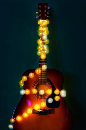 Guitar with Christmas lights with a soft focused decorated Christmas Tree in the background