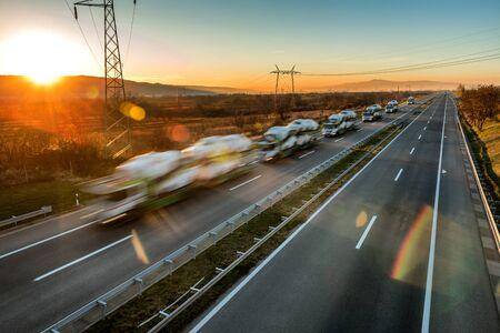 Camiones transportadores de automóviles en línea en una Sunset Highway. Camiones transportadores de automóviles: unidad de movimiento rápido borroso en la autopista al atardecer