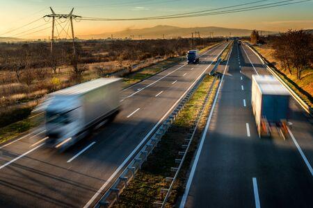 Camiones de reparto en conducción de alta velocidad en una carretera a través del paisaje rural. Unidad de movimiento borroso rápido en la autopista. Escena de carga en la autopista.
