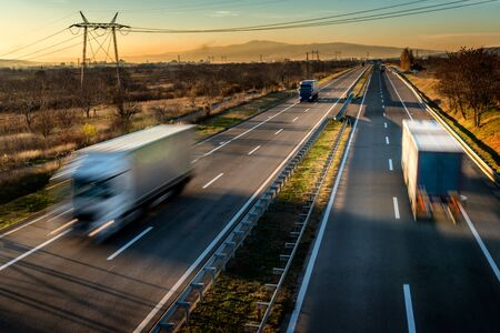 Ciężarówki dostawcze z dużą prędkością jazdy na autostradzie przez wiejski krajobraz. Szybki niewyraźny ruch na autostradzie. Scena towarowa na autostradzie