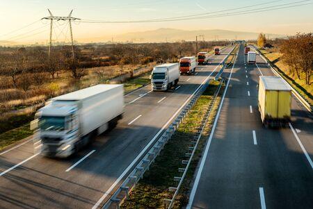 Convoglio di camion di consegna in guida ad alta velocità su un'autostrada attraverso il paesaggio rurale. Unità di movimento veloce sfocata in autostrada. Scena del carico sull'autostrada Archivio Fotografico