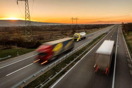 Levering vrachtwagens en auto's in hoge snelheid rijden op een snelweg door landelijk landschap. Snelle wazig beweging rijden op de snelweg. Vrachtscène op de snelweg Stockfoto