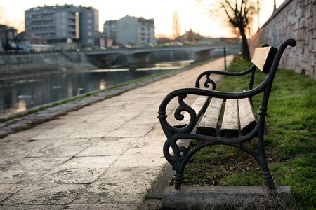 Bench at the promenade by the river bank in the autumn sunset and with soft focused background