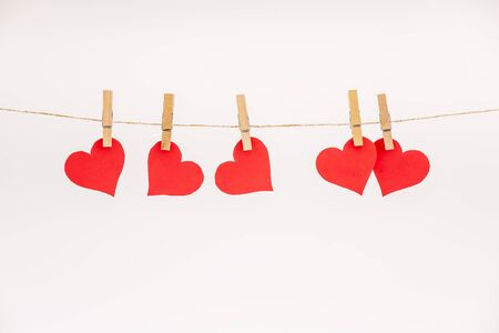 Clothes pegs and red paper hearts on rope isolated on white background. Valentines day concept Banque d'images - 138555151