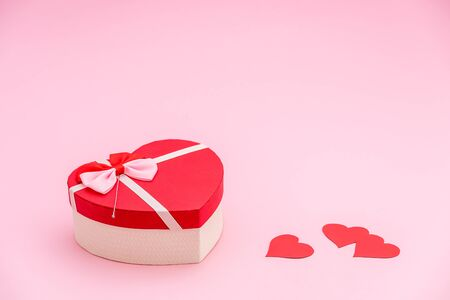 Heart shaped gift box and red paper hearts on pink pastel background. Valentines day concept