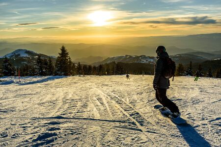 View of a ski resort piste at sunset with snowboarders and skiers, on mount Kopaonik, Serbia