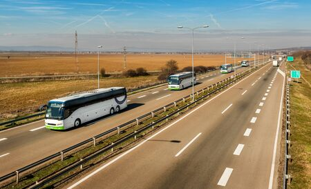 Caravan or convoy of Four white buses in line traveling on a country highway under amazing blue sky. Highway school children transportation with white buses.