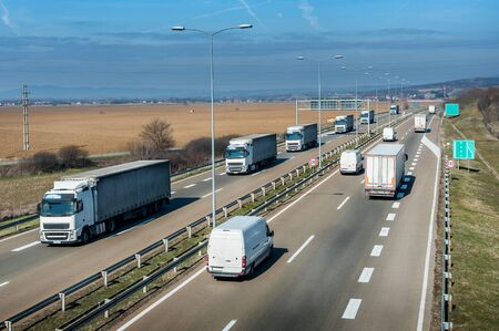 Highway transportation with a convoy of white Lorry trucks passing trucks and vans with a beautiful sunset sky Stock Photo