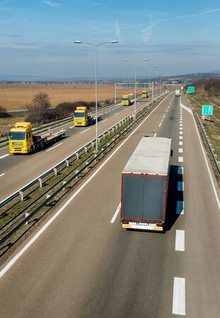 Convoy of transportation trucks passing on a highway on a bright blue day. Highway transportation with white lorry tracks