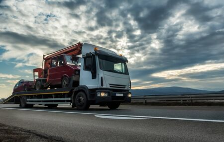 Tow truck or Flatbed truck towing two vehicles at dramatic sunset on a highway