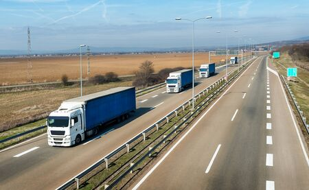 Convoy or caravan of transportation trucks on a highway on a bright blue day. Highway transportation with lorry trucks